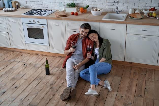 モダンなキッチンの床に座っている若い幸せなロマンチックなカップルの白人男性と女性が大好きです