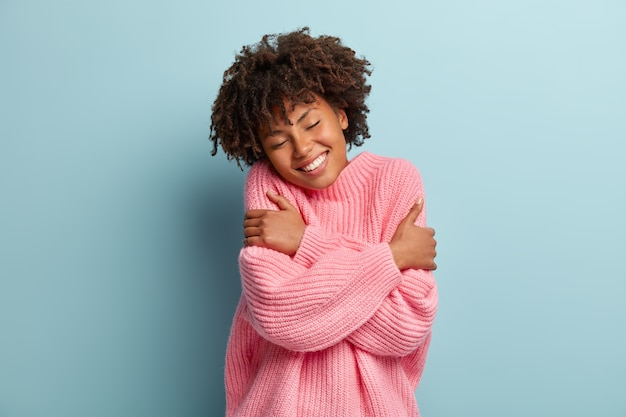 자신의 개념을 사랑하십시오. 사랑스러운 웃는 여자의 사진은 자신을 포용하고, 자존감이 높고, 즐거움에서 눈을 감습니다.