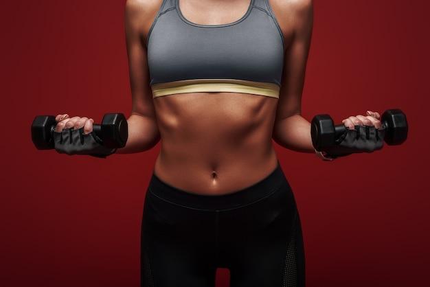 Любите себя достаточно, чтобы работать усерднее, спортсменка держит гантели стоя