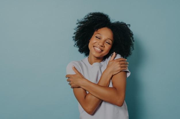 Люби себя. счастливая милая молодая африканская женщина с закрытыми глазами, обнимая себя, трогая плечи и наклоняя голову, стоя в помещении у синей стены с копией пространства для текста