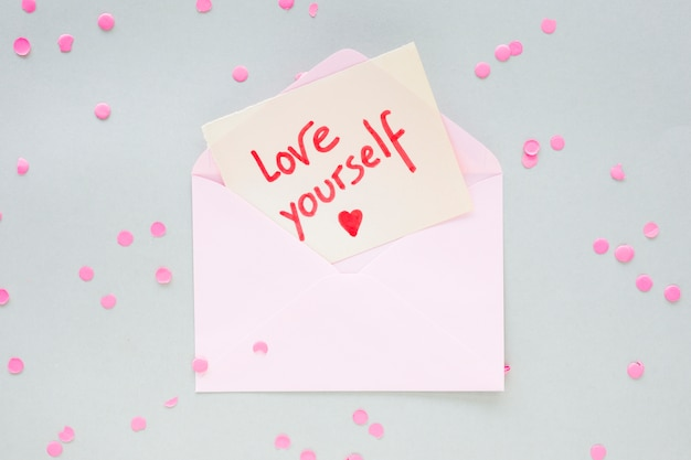 Love yourself inscription on paper in envelope