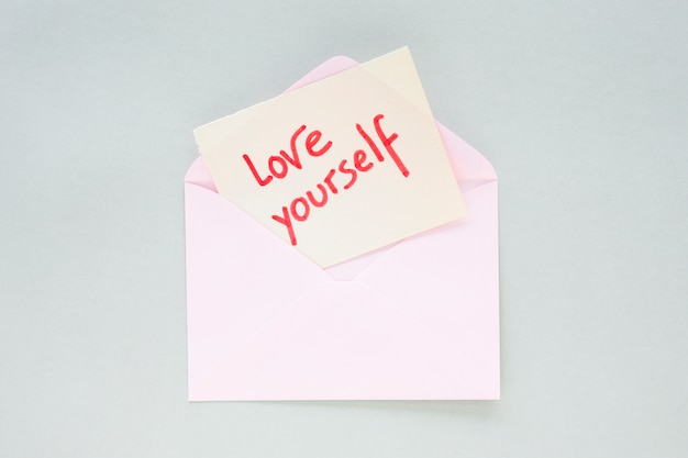 Love yourself inscription on paper in light envelope