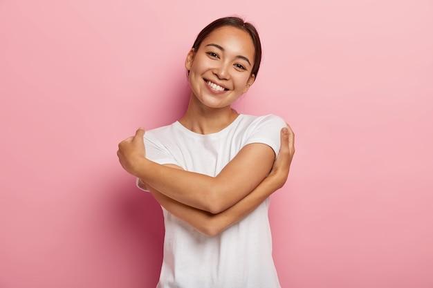 자신을 사랑하십시오. 꽤 기쁜 아시아 소녀가 자신을 포용하고, 편안함과 보살핌을 느끼고, 머리를 기울이고, 흰색 티셔츠를 입고, 화장을하지 않고, 장미 빛 벽에 고립되어, 연인에 대해 생각하고, 따뜻한 팔에 있기를 원합니다.