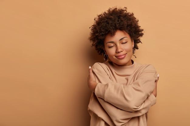 자신을 사랑하십시오, 자기 수용. 부드러운 사랑스러운 아프리카 계 미국인 여성이 손을 교차하고 몸을 감싸고 머리를 기울이고 눈을 감습니다.