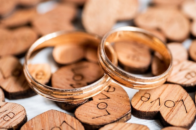 Пара золотых обручальных колец на деревянных сердечках с выжженной надписью love на белом фоне.