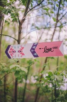 Декоративная стрелка-указатель с надписью «love» висит на ветке дерева на природе