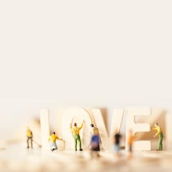 Люди готовят день святого валентина с текстом love и мягкими пастельными тонами.