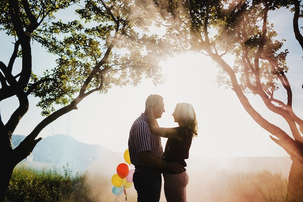 Lovely adult couple with colorful balloons stands under a tree