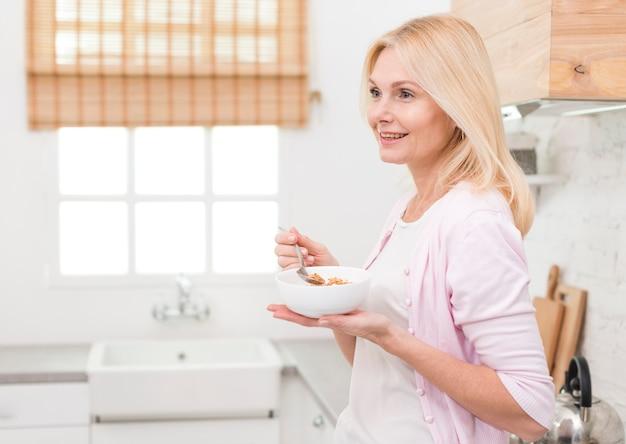 キッチンで朝食を提供する素敵な大人の女性