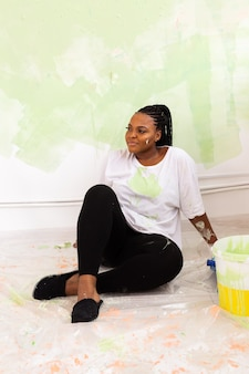 Lovely african american housewife painting wall. renovation, redecoration and repair concept.