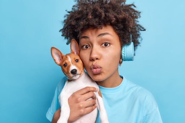 Lovely african american woman carries small breed dog near face keeps lips folded as if wanting to kiss someone loves her favorite pet have walk dressed casually listens music in stereo headphones
