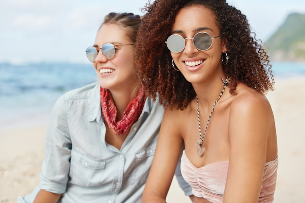 Lovely african american woman with dark skin and curly hair, has positive smile, wears sunglasses, sits near her girlfriend who enjoys seascape, enjoy calm atmosphere at beach. friendship concept