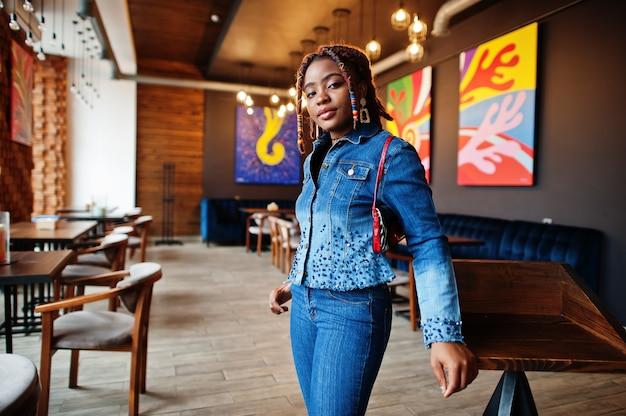 カフェで青いスタイリッシュなジーンズのジャケットのドレッドヘアを持つ素敵なアフリカ系アメリカ人の女性。屋内で美しくクールなファッショナブルな黒人少女。