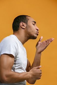 Lovely afro-american man is making air kiss against orange background