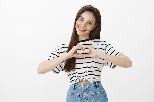 Милая и очаровательная молодая женщина показывает жест сердца и улыбается, признается в сочувствии или любви