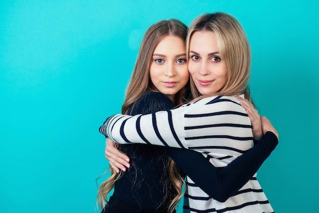 スタジオで青い背景に彼女の最愛の母親を抱き締める素敵で美しい若いティーンエイジャーの女の子。家族の幸福と母の日の概念