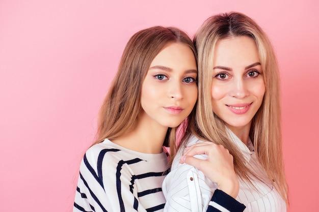 Прекрасная и красивая молодая девушка-подросток, обнимая свою любимую мать на розовом фоне в студии. концепция семейного благополучия и день матери.
