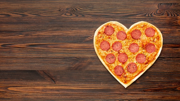 Lovely arrangement for valentines day dinner with heart shaped pizza and copy space