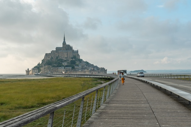 Lovely arrival on the wooden path to mont saint-michel in the manche department, normandy region, france