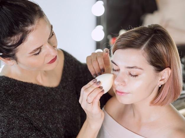 Lovely artist working in makeup studio