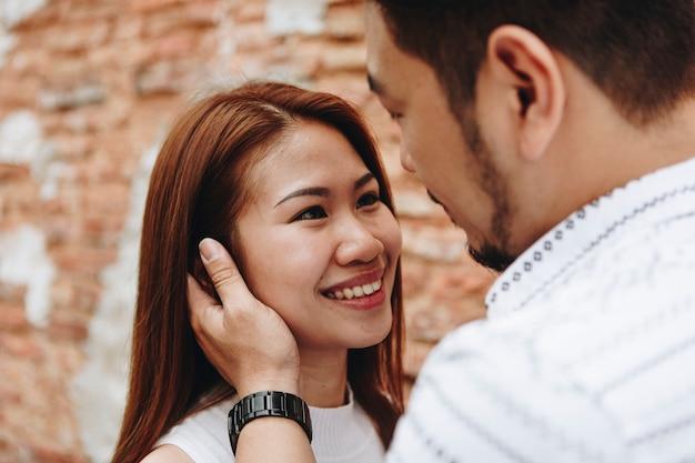 レンガの壁の素敵なアジアのカップル