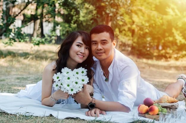 彼らの胃の上に横たわって、公園でピクニックをしている素敵なアジアのカップル。花束を持って、木の影で白い服を着て休んでいる女性。