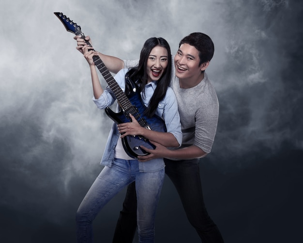 Lovely asian couple playing guitar