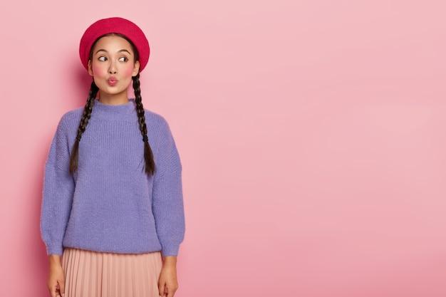 사랑스러운 아시아 여성 모델은 입술을 둥글게 유지하고, 뺨이 붉고, 외모가 매력적이며, 남자 친구에게 키스하고, 세련된 옷을 입고, 옳게 보이고, 실내에 서 있습니다.