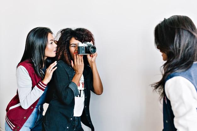 素敵なアジアの女の子は、彼女の友人の写真を撮る魅力的なアフリカの写真家に見えます。黒の衣装で巻き毛の女性の前でカメラにポーズをとるブルネットの若い女性。