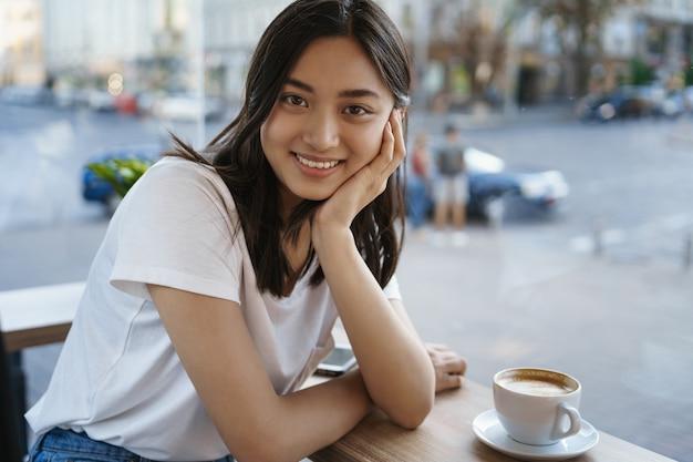 커피 테이블에 앉아 사랑스러운 아시아 소녀, 카푸치노를 마시고 웃고.