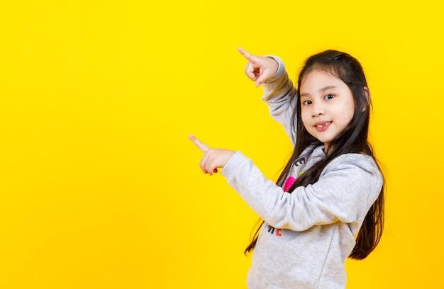 스웨터를 입은 사랑스러운 아시아 소녀는 행복한 아이의 고립된 초상화에서 겨울 혜택을 제안하기 위해 복사 공간에서 원하는 메시지를 두 손가락으로 가리키도록 손짓을 하며 웃고 있습니다.