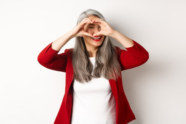 Lovely asian middle-aged woman with grey hair, wearing red blazer, showing heart sign and peeking throught it, i love you gesture, standing over white background.