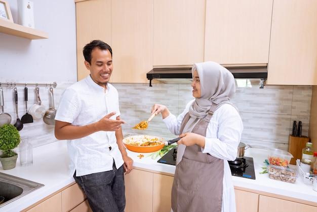 素敵なアジアのイスラム教徒のカップルがキッチンで一緒に食事を作るのを楽しんでいます