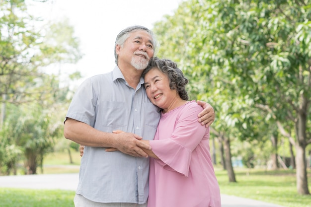 Lovely asian seniors couple embracing together in the park in the morning.