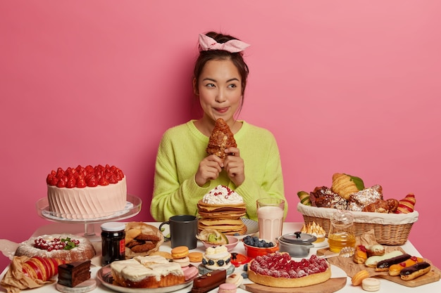 Lovely asian woman enjoys festive gathering, sits at table with many cakes, bites delicious croissant, being sweet tooth, licks lips isolated over pink background.