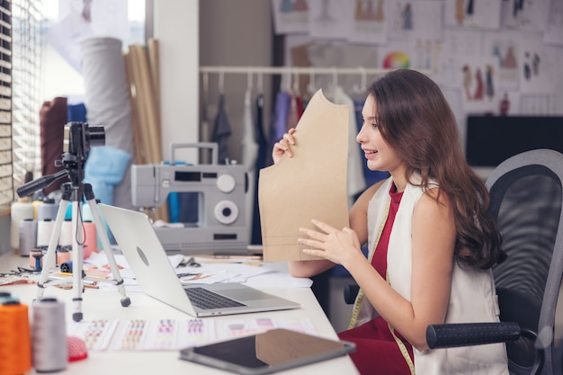 A lovely asian woman fashion designer sits at her workstation in her studio, stares at the webcam, and speaks through video call.