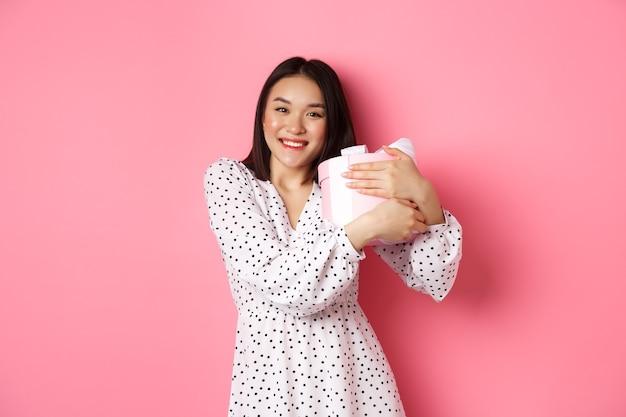 사랑스러운 아시아 여성이 그녀의 선물을 껴안고 감사하게 웃으며 서 있는 발렌타인 데이 선물을 받습니다.