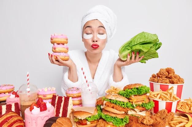 사랑스러운 아시아 여성은 눈을 감고 입술을 접고 키스하고 싶어하며 도넛을 들고 녹색 상추는 건강에 좋은 음식과 건강에 해로운 음식 사이에서 주저합니다