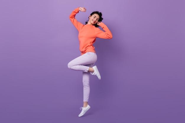 한쪽 다리에 서있는 사랑스러운 아시아 여자. 보라색 배경에 점프 매력적인 세련 된 일본 여자의 전체 길이보기.