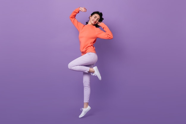 Lovely asian woman standing on one leg. full length view of attractive stylish japanese woman jumping on purple background.