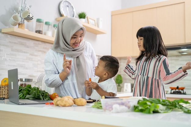 딸과 아들이 금식을 깨는 라마단 동안 저녁 식사를 요리하는 사랑스러운 아시아 여자