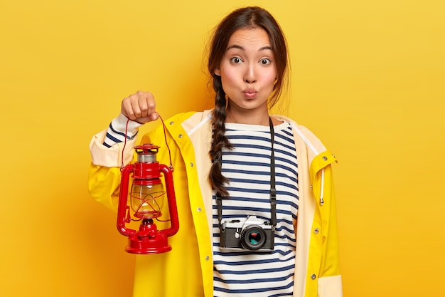 Lovely asian woman with long dark hair, holds red torch, dressed in casual yellow raincoat and striped jumper, being active tourist, hikes during summertime, captures moment with retro camera