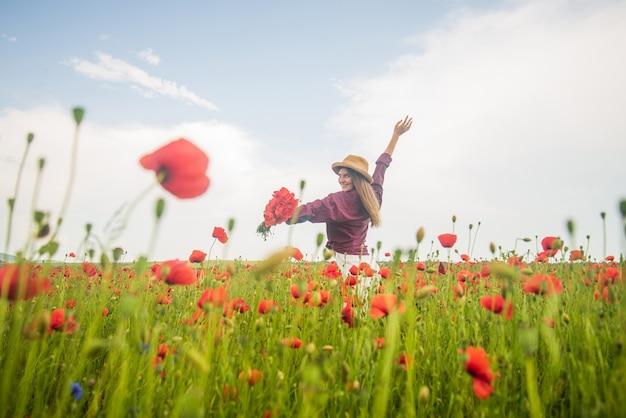 素敵な雰囲気。季節の美しさの風景。帽子をかぶった少女は牧草地を歩きます。休暇。自由の感覚。美しい女性は、フィールドで赤いポピーの花の花束を収集します。夏または春の自然。