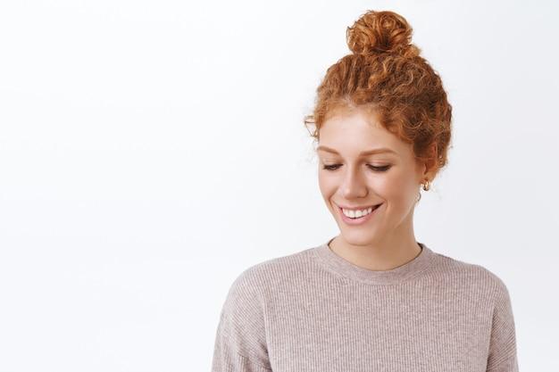 세련된 블라우스를 입은 사랑스럽고 매력적이고 부드러운 빨간 머리 곱슬머리 여성, 내려다보고, 칭찬에 얼굴을 붉히며, 행복하고 겸손하게 서서 웃고, 행복하게 웃고, 흰 벽에 서 있습니다