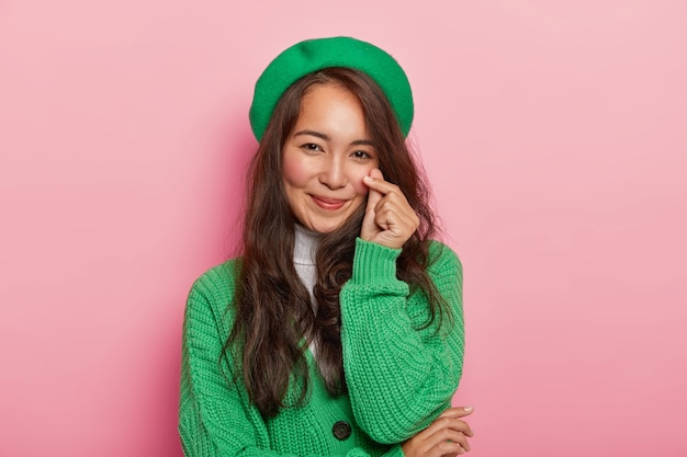 Lovely attractive brunette woman makes korean like gesture, shapes little heart with fingers, has long dark straight hair, wears green beret and jumper on buttons
