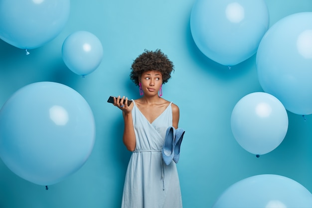 Lovely attractive thoughtful young afro american woman prepares for date, holds smartphone in hand and waits for call from boyfriend, dresses blue dress and shoes, stands indoor near balloons