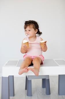 Прекрасная девочка ест мороженое на столе