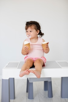 Lovely baby girl eating ice cream on table