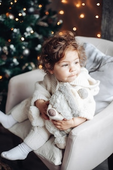 Lovely baby with curly hair in white sitting in chair with teddy bear.