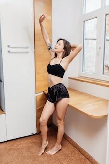 Прекрасная красивая брюнетка растягивается на кухне утром после сна